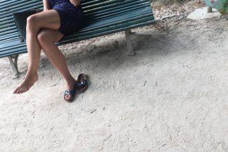 Une femme en claquettes dans un jardin public