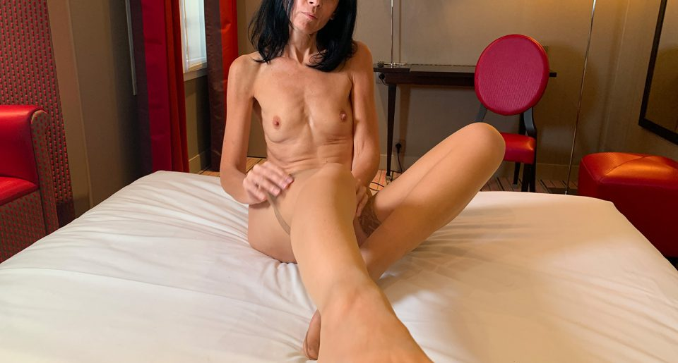 A mature woman with a hairy pussy shows her feet