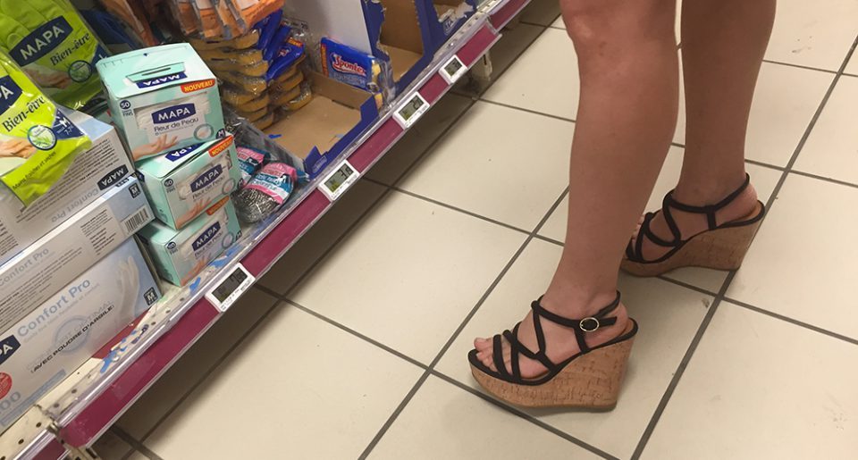 A hot MILF wears sandals in a supermaket