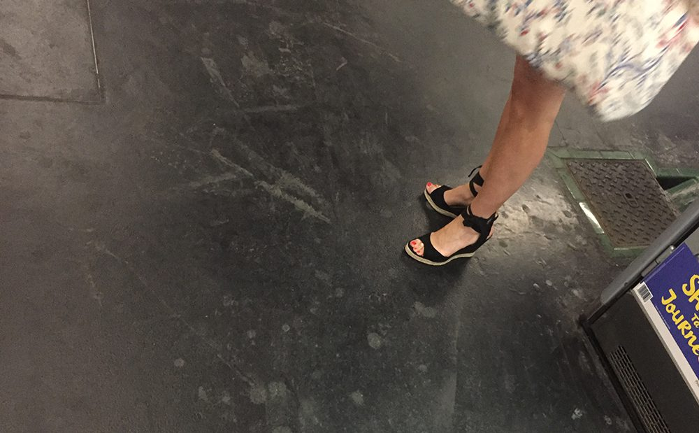 A nice girl in sandals is waiting for the subway