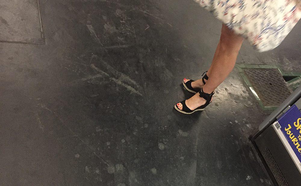 Une femme en sandales sexy attend le métro