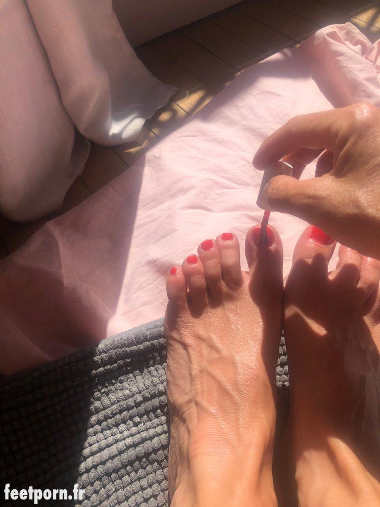 Elle se vernit en rouge les ongles des pieds