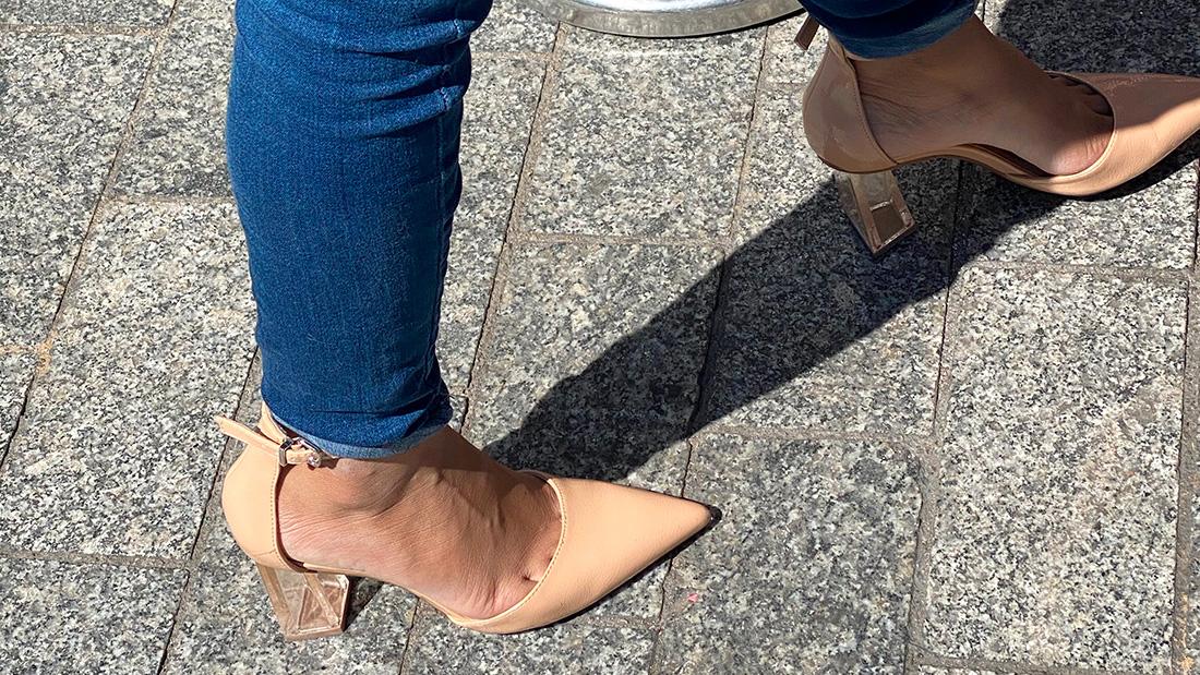 Une jeune métisse avec des chaussures à talons transparents qui laissent voir ses orteils