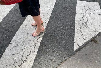 Une femme sexy avec des mules transparentes traverse la rue