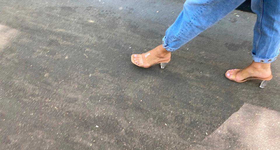 Une fille sexy avec des mules transparentes marche dans la rue