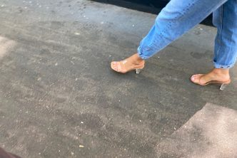 A sexy girl with transparent mules walking in the street