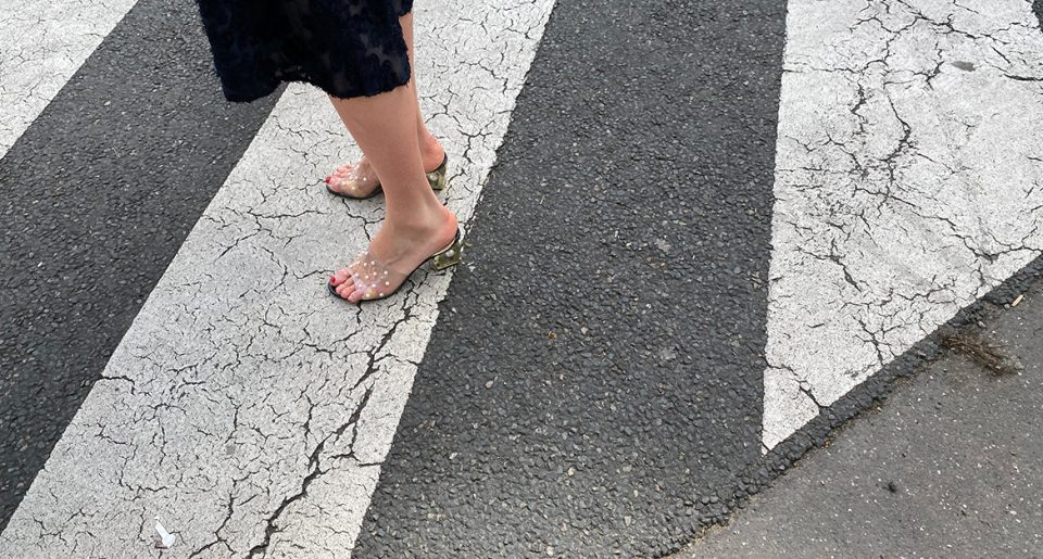 A sexy woman with transparent mules in the street