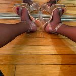 Ma copine avec des bas noirs et de chaussures transparentes écarte les jambes