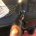 Une femme s'exhibe dans le train avec des bottes en cuir et des collanst noirs
