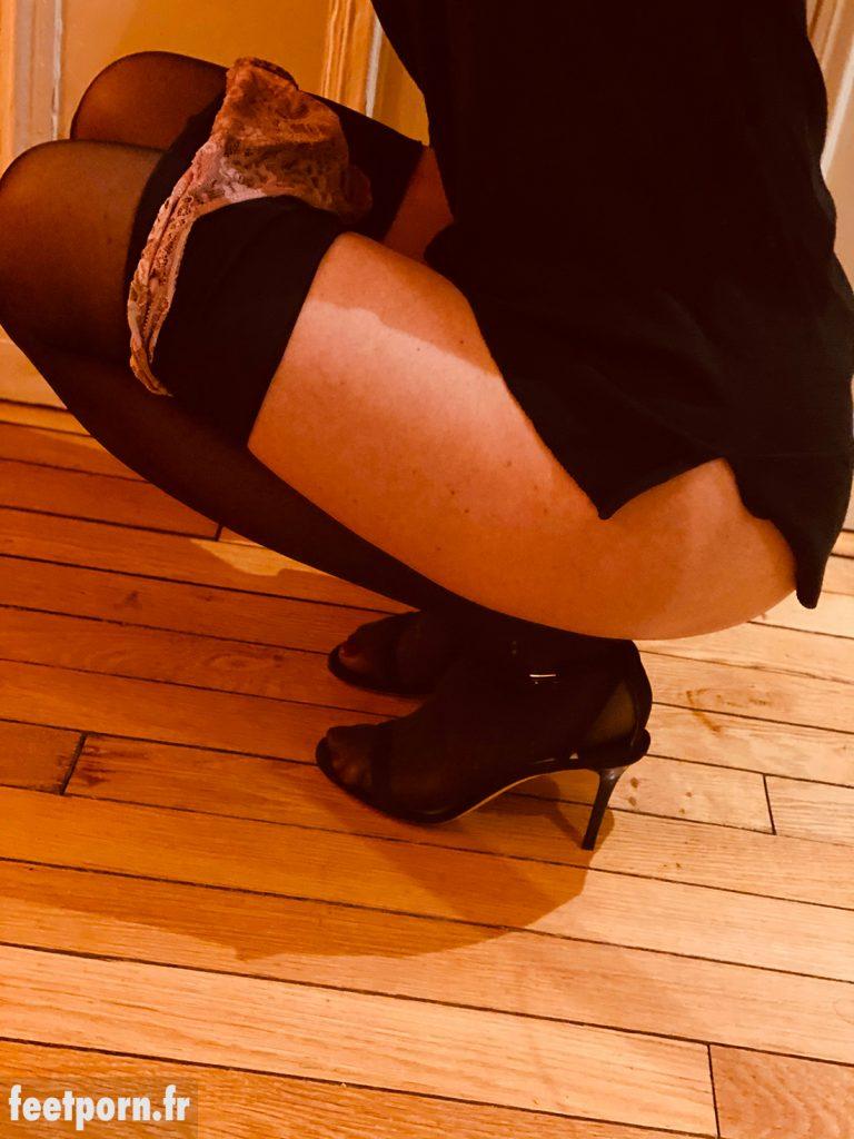 Elle porte des collants noirs et des sandales de luxe