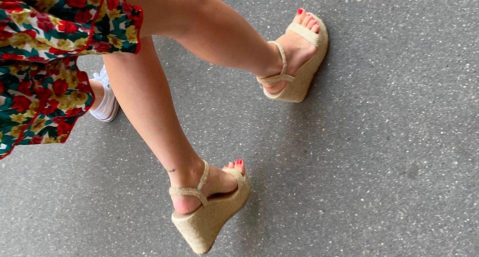 Une jeune femme avec un tatouage derrière la cheville et des sandales compensées